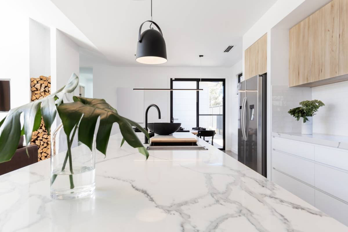 Marble countertop in the center of bright white kitchen.